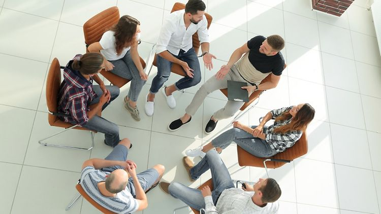 people sitting on chairs in a circle and talking