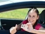 Woman showing her driving licence out of the window of her car