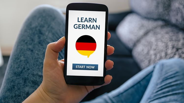 A woman sitting on a sofa and holding a smartphone with a learn german app on screen.
