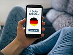 A woman sitting on a sofa and holding a smartphone with a learn german app on screen. / © maicasaa / Shutterstock.com